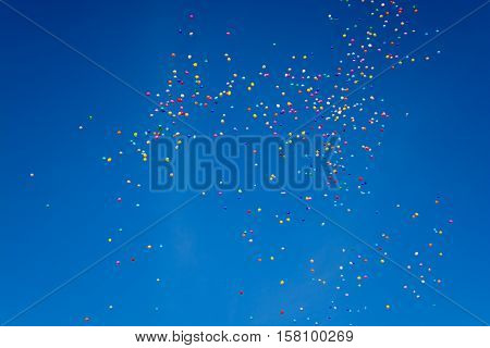 Hundreds of colorful ballons are flying through the blue cloudless sky
