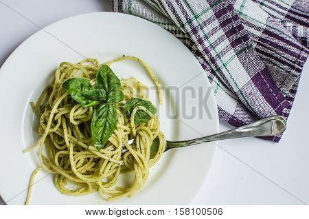 Close up italian pasta spaghetti with homemade green pesto sauce and basil leaf with a fork. Delicious healthy vegetarian food. Italian food concept. Top view.