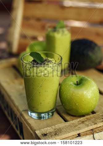 Organic green detox smoothie or shake made of apple avocado banana and chia decorated with leaf of mint. With fresh fruits on wooden background. Selective focus. Vertical.