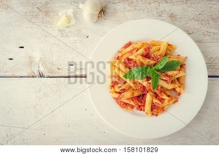 Italian Wholemeal Pasta Penne with Tuna and Basil. Fresh pasta with tuna and tomato sauce on white wooden background with place for text. Italian cuisine concept. Copy space. Top view.