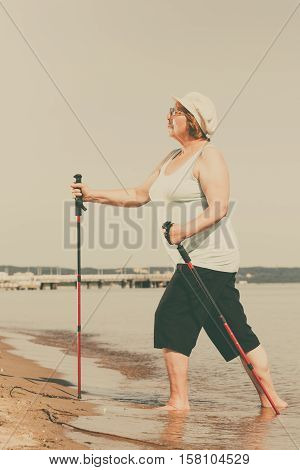 Senior woman practicing nordic walking on sea shore Active elderly female enjoying sunny summer day. Healthy lifestyle in old age. Toned image