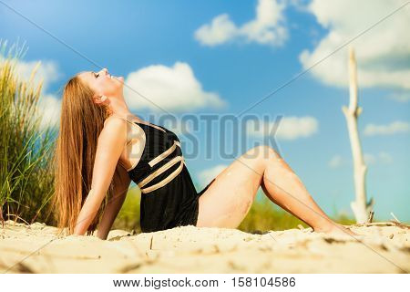 Summer vacation day freetime concept. Sitting woman body sunbathing delight on beach seaside.