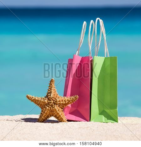 Shopping Bags And Starfish On Sand Against Turquoise Caribbean Sea Water