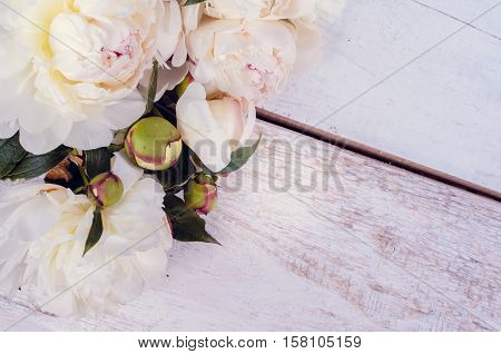 Peony background. White peonies on wooden table with place for text. Spring flowers peonies. Happy Mothers Day. Mother's Day greetings card. Mothers Day gift. Valentines Day. Copy space. Toned image.