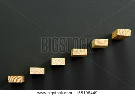 Going up concept using wooden stairway over black background