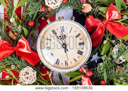 Green mistletoe and old clock on wood desk. Nature background. Christmas plant