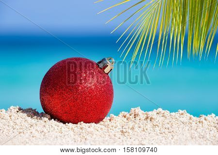 Red Fir Tree Decoration Ball On Sandy Beach With Palm Tree Leaves