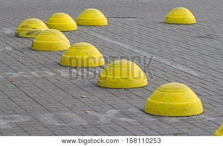 Yellow concrete hemispheres prohibiting parking barrier on pavement.