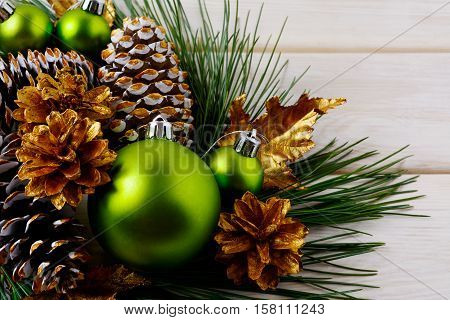 Christmas green ornaments and golden decorated pine cones. Christmas table centerpiece with golden decor. Christmas background.