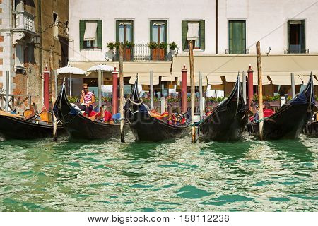 Venice Italy - September 8 2016: Gondolier making agreement about making a deal with touristic group. A row of gondolas waiting for clients in Venice Italy