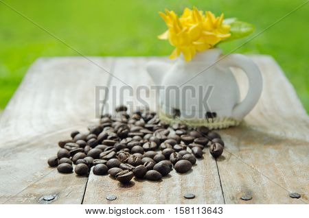 Coffee Beans On Grunge Wood Background With Ixora Flower Pot And Natural Light And Garden View