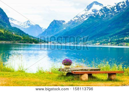 Tourism vacation and travel. Serene mountains landscape rest place table with bunch of flowers on fjord shore Olden village in Sogn og Fjordane county Norway Europe.