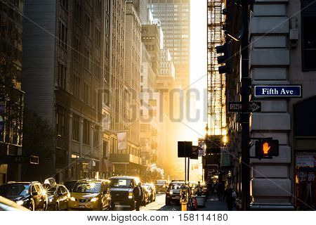 NEW YORK NEW YORK/ UNITED STATES OF AMERICA - NOVEMBER 14. 7:07 am Morning of the Supermoon. Closest lunar passing since 1948. Sun rising filling 39th st. with a golden wash of light. daily commuters are just starting to arrive and trafic starting to buil