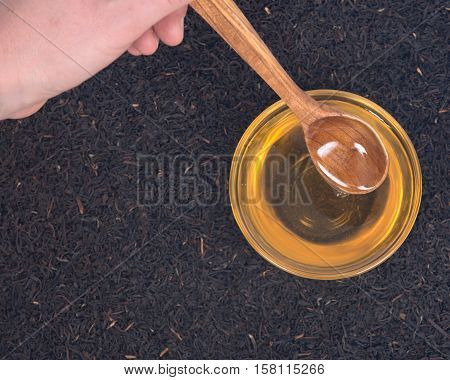 Organic amish farm pure honey in bowl and camellia assam tea with wooden spoon