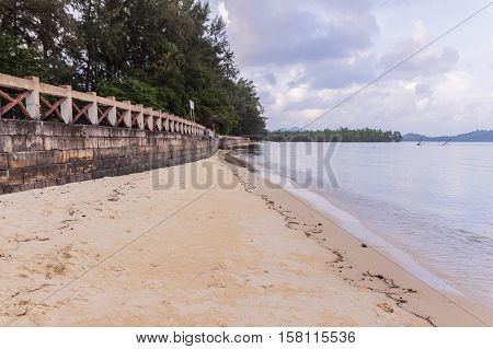 Beachside concrete retaining wall when low tide in the evening Phuket Thailand