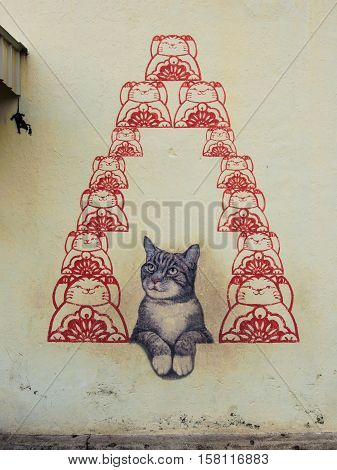 Georgetown, Penang, Malaysia - February 18, 2015: The mural of cat for luck, street art on wall by local artist in George Town, Penang, Malaysia.