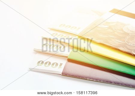 Business, finance savings or mortgage background concept ; Thai money and savings account passbook on white background