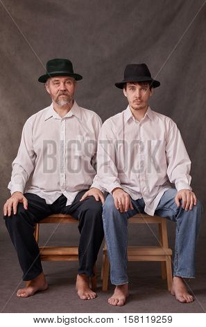 Two men sitting side by side on stools. Studio photography