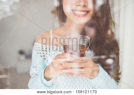Portrait of a young asian woman drinking her morning tea over a breakfast at home.