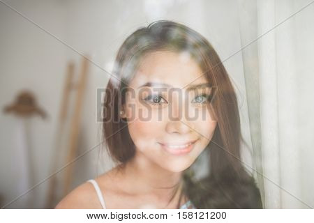 Asian woman looking through a window. Young asian woman relaxing at her home.