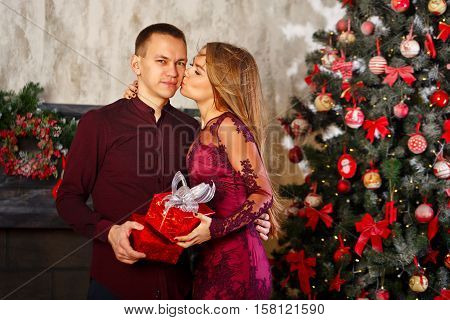 Loving couple and Christmas. Girl kissing her boyfriend in return for a Christmas gift. In the background a beautiful Christmas tree.