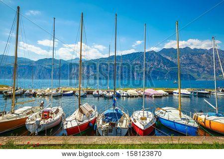 Sailing boats yachts on Garda lake. Veneto region. Italy. Landscape of marine regatta with floating in the harbor high Alpine mountains background