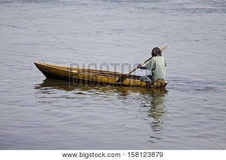 JUBA, SOUTH SUDAN-FEBRUARY 19 2013: unidentified man paddles traditionally made canoe on the White Nile through Juba, capital of South Sudan