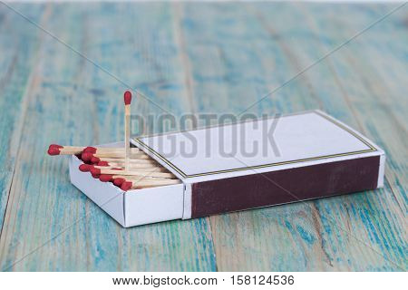 Red Matchbox on color wood table background