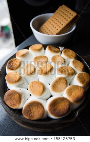 smores or baked marshmallows with chocolate syrup and graham