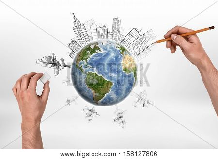 Hands of man drawing buildings and erasing trees on the globe. Deforestation. Depletion of natural resources. Urbanization.