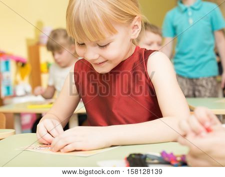 Portrait Of A Happy Smiling Girl Draws Bright Colorful Picture And Sculpts From Clay In Kindergarten