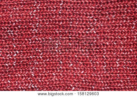 Textured background of red and white soft warm cable knit sweater fabric material