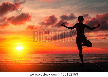 Silhouette young woman practicing yoga on the beach at surrealistic bloody red sunset.