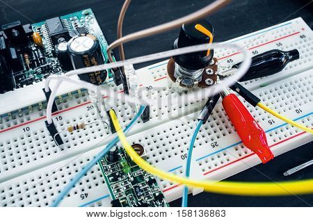 Close-up of breadboard with electronic components. New program development in laboratory with special equipment. Electronics construction concept