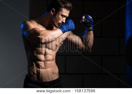 Shirtless Muscular Boxer With Punching Bag In Gym