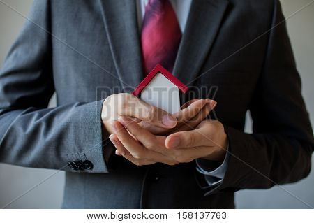 Business Man In Suit Using Hands Covering And Protecting House - Business Mortgage, Property Loan, H
