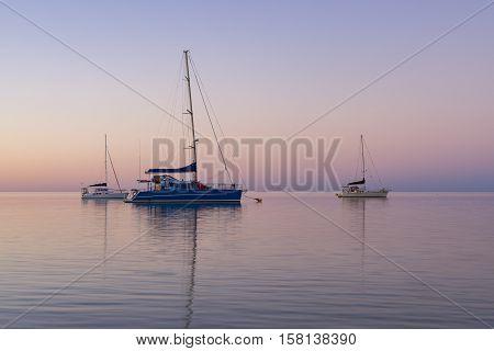 Yachts in still water during sunset at Monkey Mia, Western Australia, Australia.