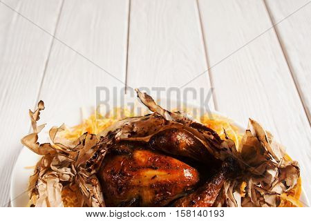 Baked chicken in paper cover, free space. Roasted poultry on white wooden background, copy space for text or advertisement. Junk fast food, american cuisine, fat, menu concept