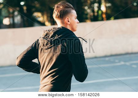 Side view portrait of exercising man outside. Close-up profile photo of running sprinter on open-air stadium. Everyday jog , healthy lifestyle concept