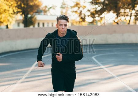 Young handsome man running down stadium track. Professional sprinter training for marathon. Sport, competition, persistence, goal, motivation concept
