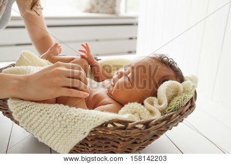 Close-up of newborn child playing with mother. Mom touching her little baby in wicker cradle, white background, free space