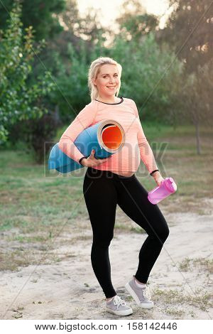 Smiling pregnant woman ready for fitness outdoor. Gravid lady posing with karemat and bottle of water. Health and body care, sport, pregnancy concept