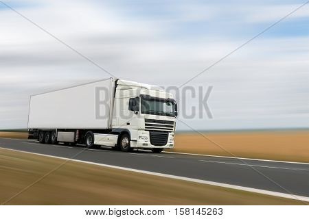 white heavy truck on a road motion blur