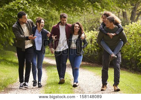 Young couples walking and piggybacking in a country lane