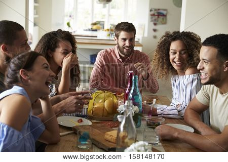 Young adults laughing as they talk at a table over lunch