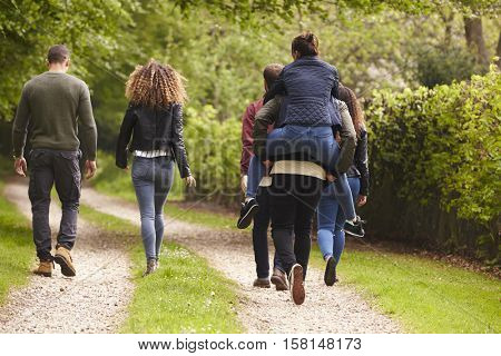 Friends walk and piggyback in a country lane, back view