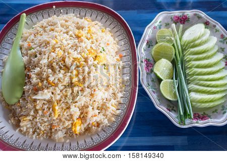 A menu of fried rice with crabmeat in a dish with side dish of vegetables.