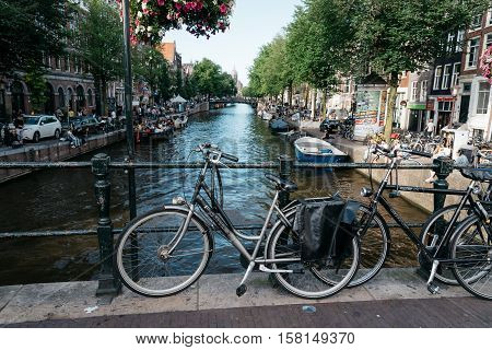 Amsterdam Netherlands - August 1 2016: Bicycles in a bridge over the canals in Red Light District of Amsterdam.