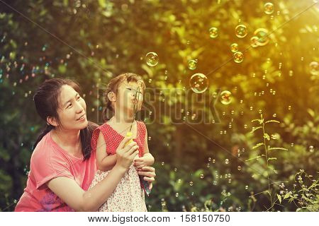 Little asian lovely girl and her mother blowing soap bubbles on blurred nature background. Outdoors at the daytime with bright sunlight. Loving and happy family. Warm tone and vintage effect style.