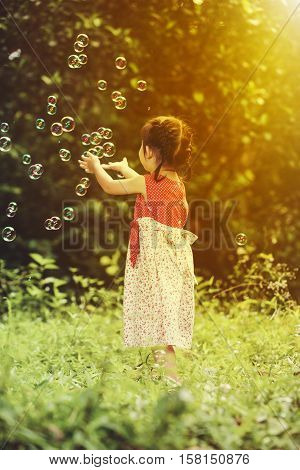 Asian Girl Catches Soap Bubbles On Nature Background. Outdoors. Back View.